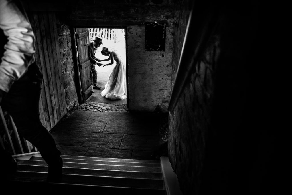 lake district documentary wedding photographer Askham Hall laughing in the door in black and white