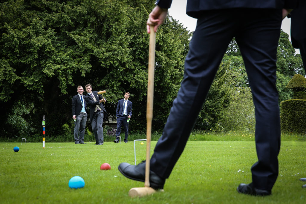 lake district documentary wedding photographer Askham Hall wedding guests playing croquet