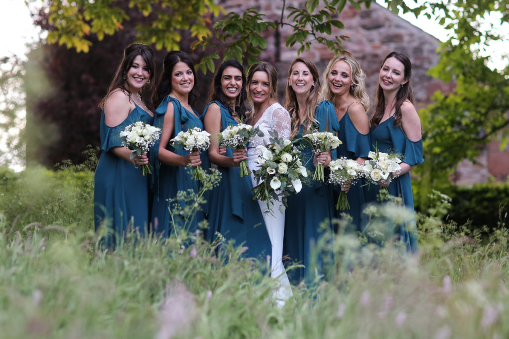 lake district documentary wedding photographer Askham Hall bride and bridesmaids in long grass