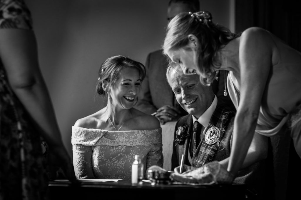 lake district documentary wedding photographer Springkell signing the register black & white