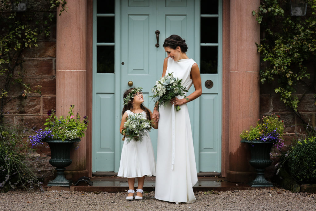 lake district documentary wedding photographer Rowley Estates bride and flower girl in door