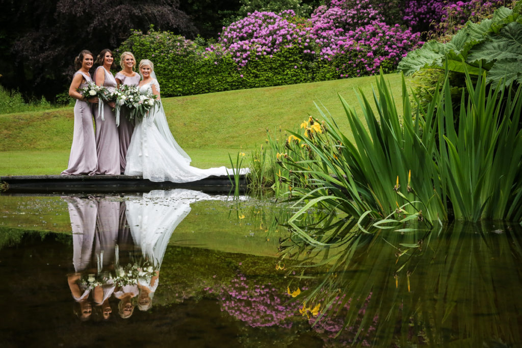 lake district documentary wedding photographer Merewood bridesmaids in a spring garden with reflection