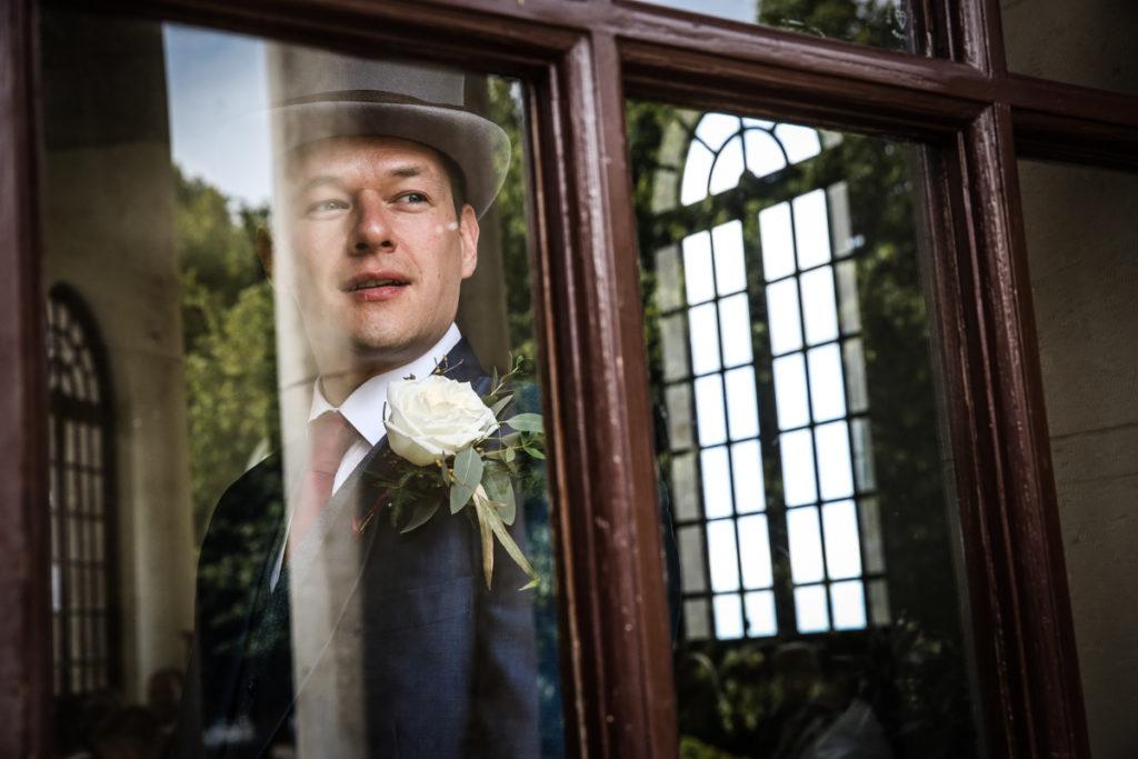 lake district documentary wedding photographer Ashton Memorial groom in window