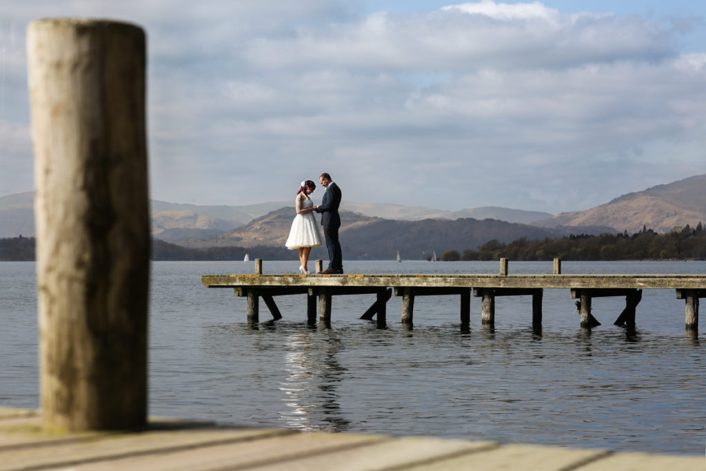 lake district documentary wedding photographer couple on jetty in the sun
