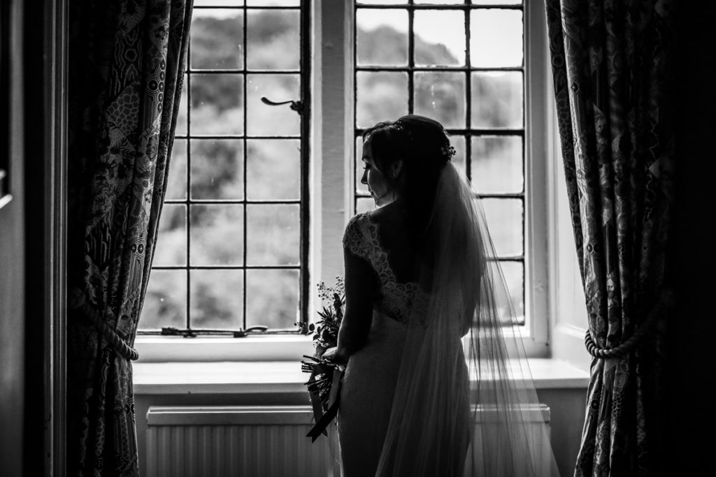 lake district documentary wedding photographer Askham Hall bride in a window black and white