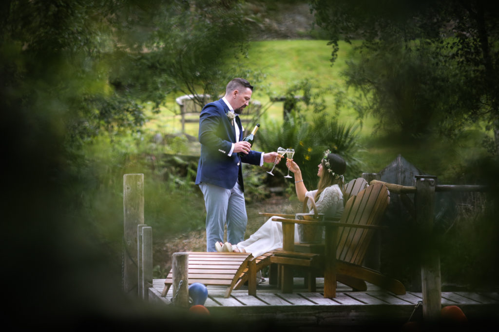 lake district documentary wedding photographer Gilpin Lake House couple on jetty with champagne