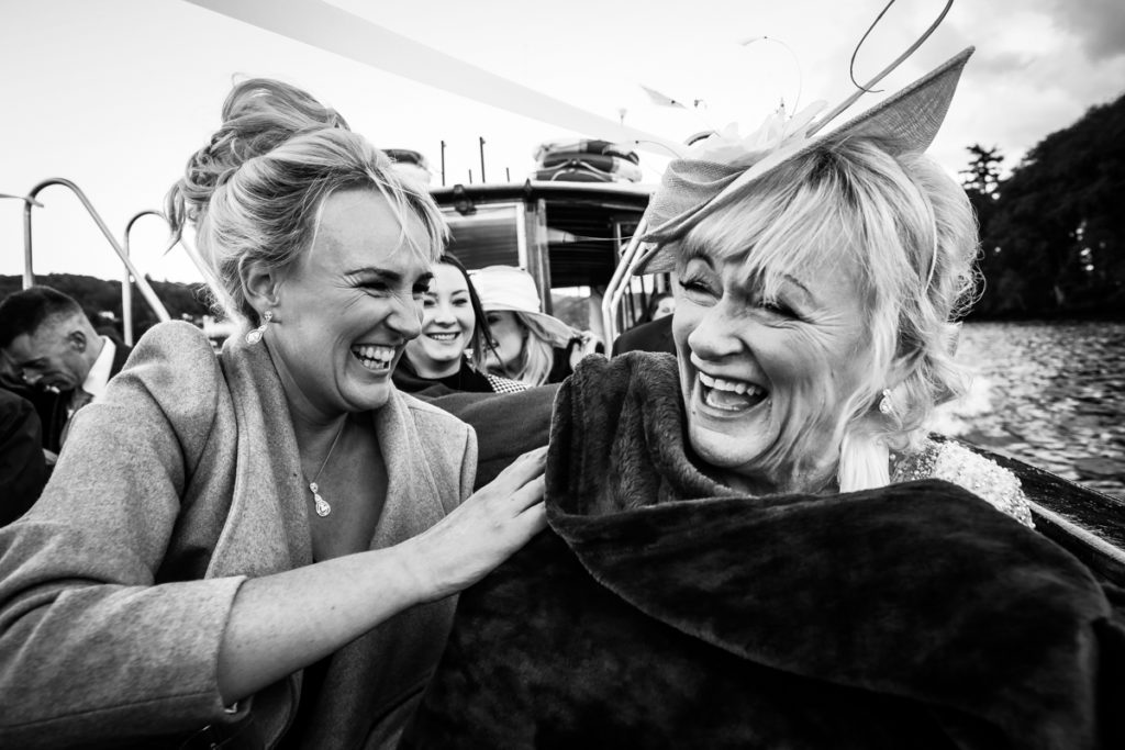 lake district documentary wedding photographer guests laughing on a boat