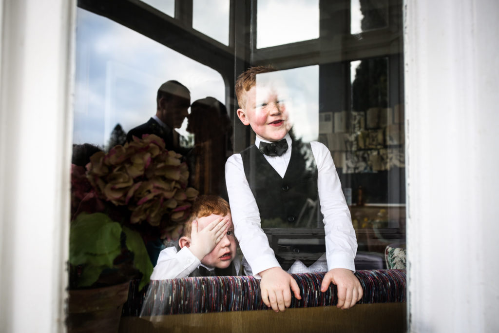 lake district documentary wedding photographer silhouette with children laughing at parents kissing in window