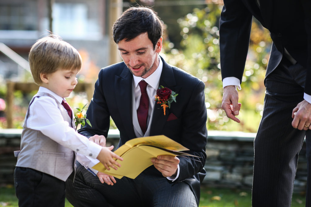lake district documentary wedding photographer Lodore Falls Hotel groom and son with book