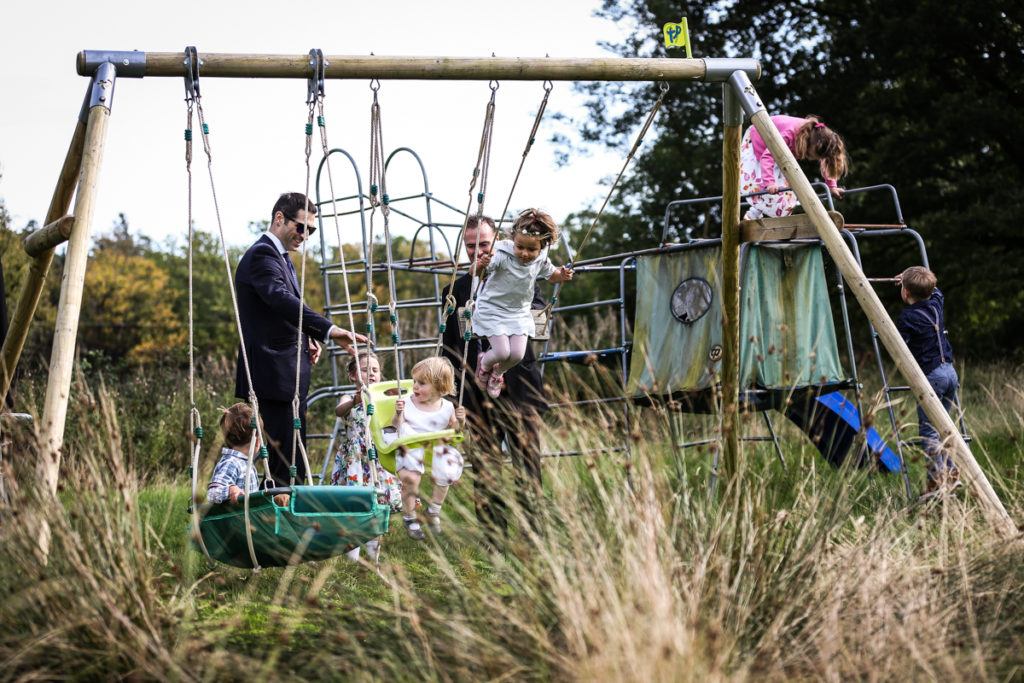 lake district documentary wedding photographer Springkell children on swing set in the summer