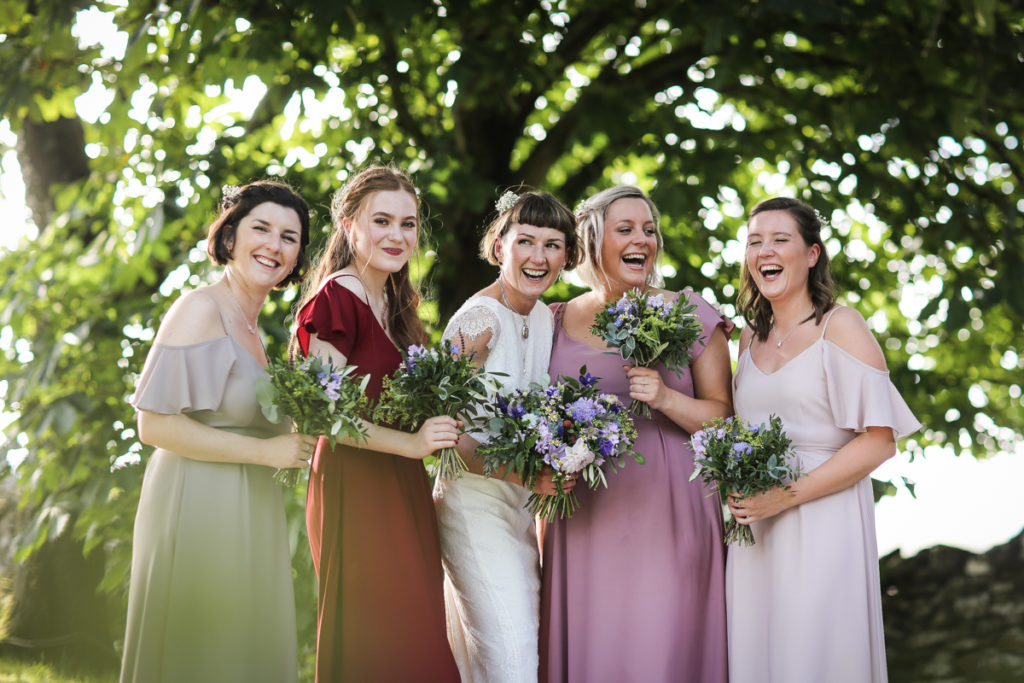 lake district documentary wedding photographer Bridesmaids laughing in front of trees