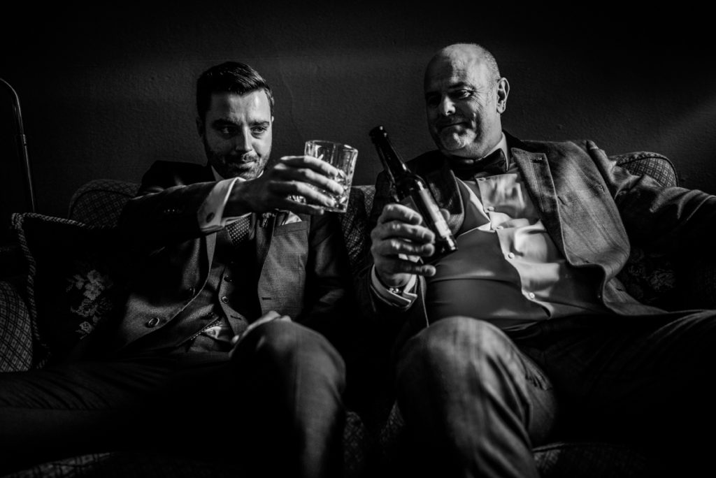 lake district documentary wedding photographer Askham hall two men drinking in black and white