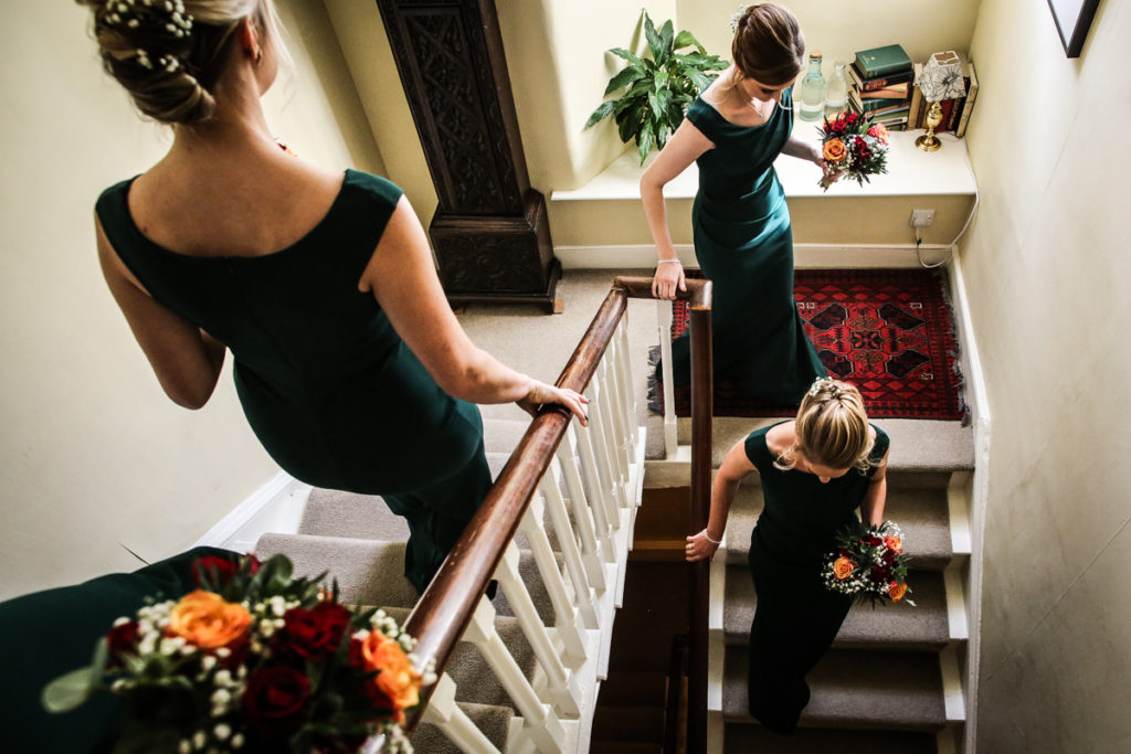 lake district documentary wedding photographer Belmount Hall bridesmaids going down the stairs