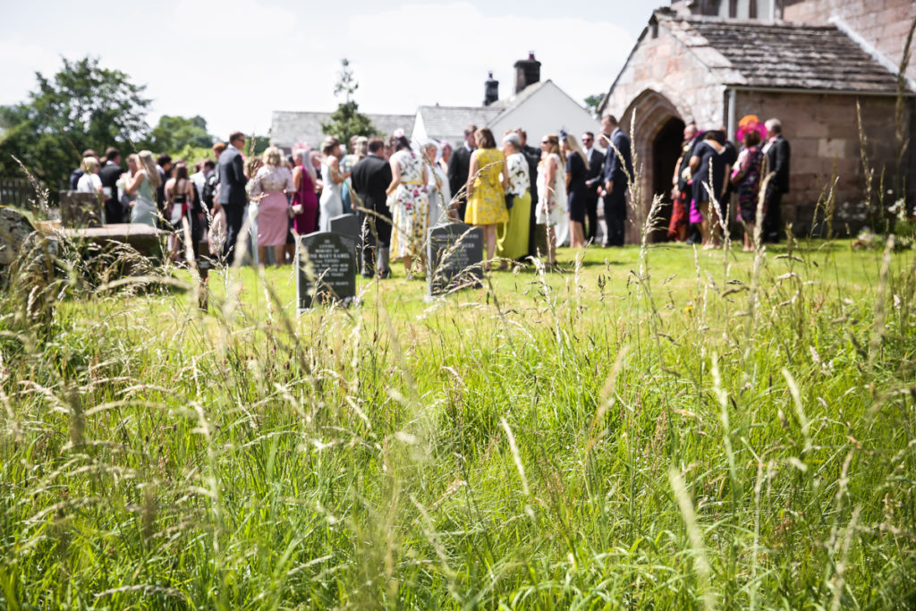 lake district documentary wedding photographer wedding guests outside the church