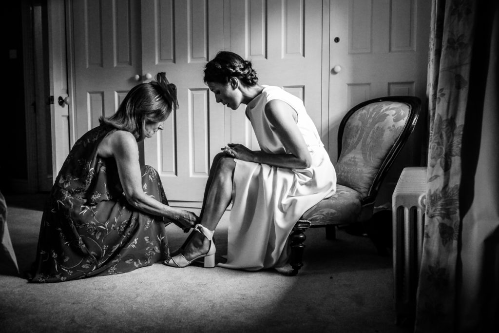 lake district documentary wedding photographer Melmerby Hall bride putting on shoes