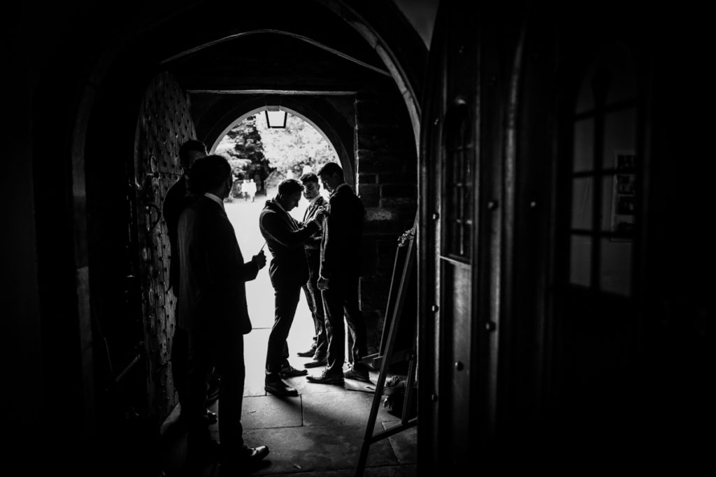 lake district documentary wedding photographer ushers and groom in the church door silhouette in black and white
