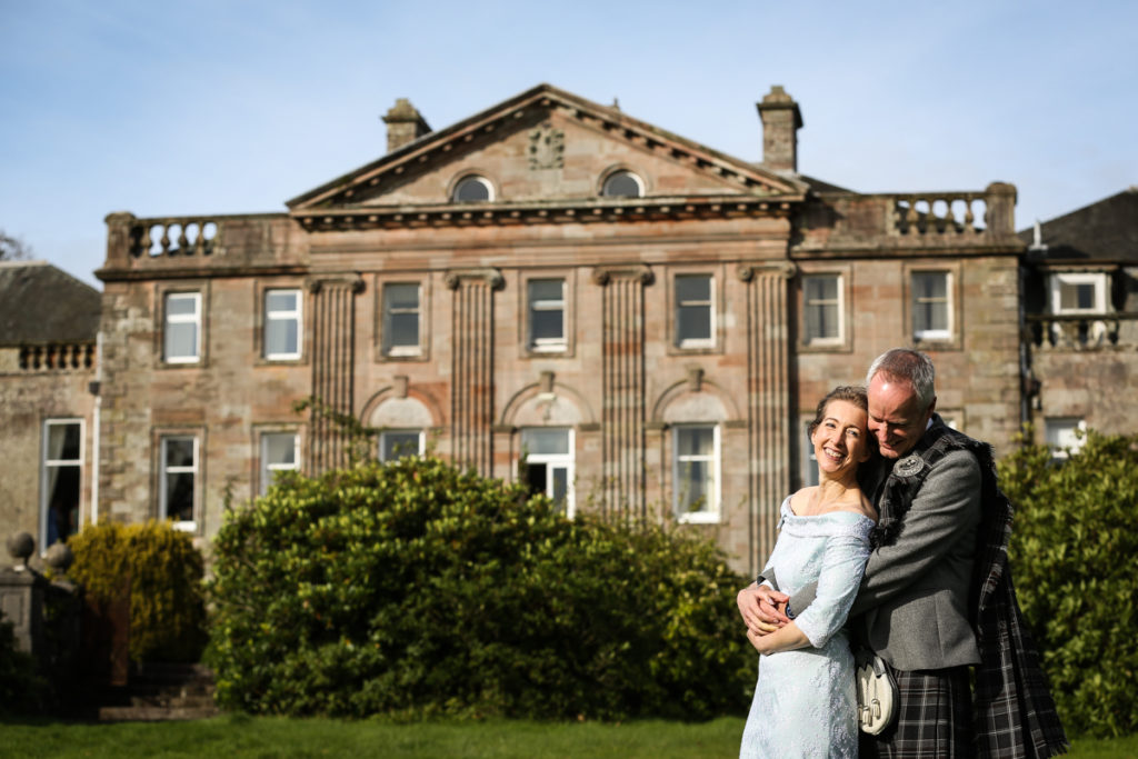 lake district documentary wedding photographer Springkell couple posing in front of the house