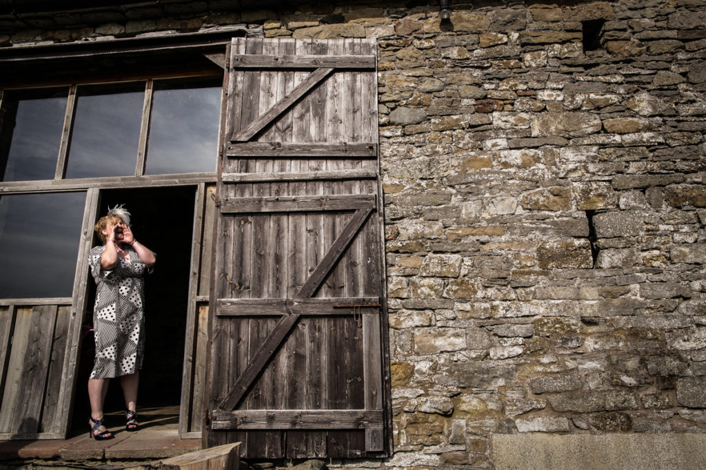 lake district documentary wedding photographer woman shouting in front of a barn