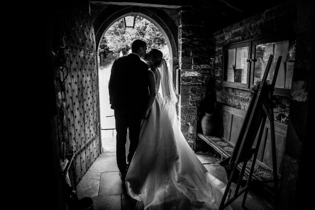 lake district documentary wedding photographer couple kissing in church door in black and white