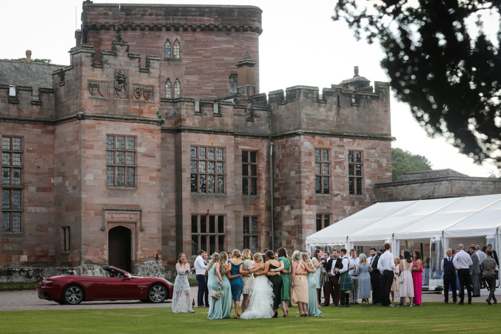 lake district documentary wedding photographer Greystoke Castle wedding guests on the lawn