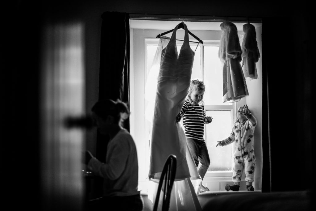 lake district documentary wedding photographer childresn playing with dress in window