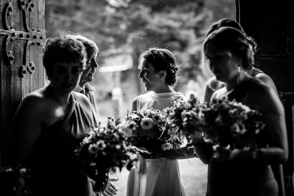 lake district documentary wedding photographer church bride and fathers entrance in black and white