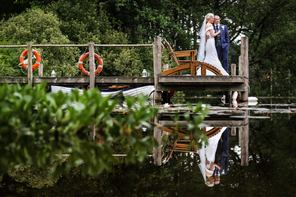 lake district documentary wedding photographer Gilpin Lake House couple on jetty portrait with reflection