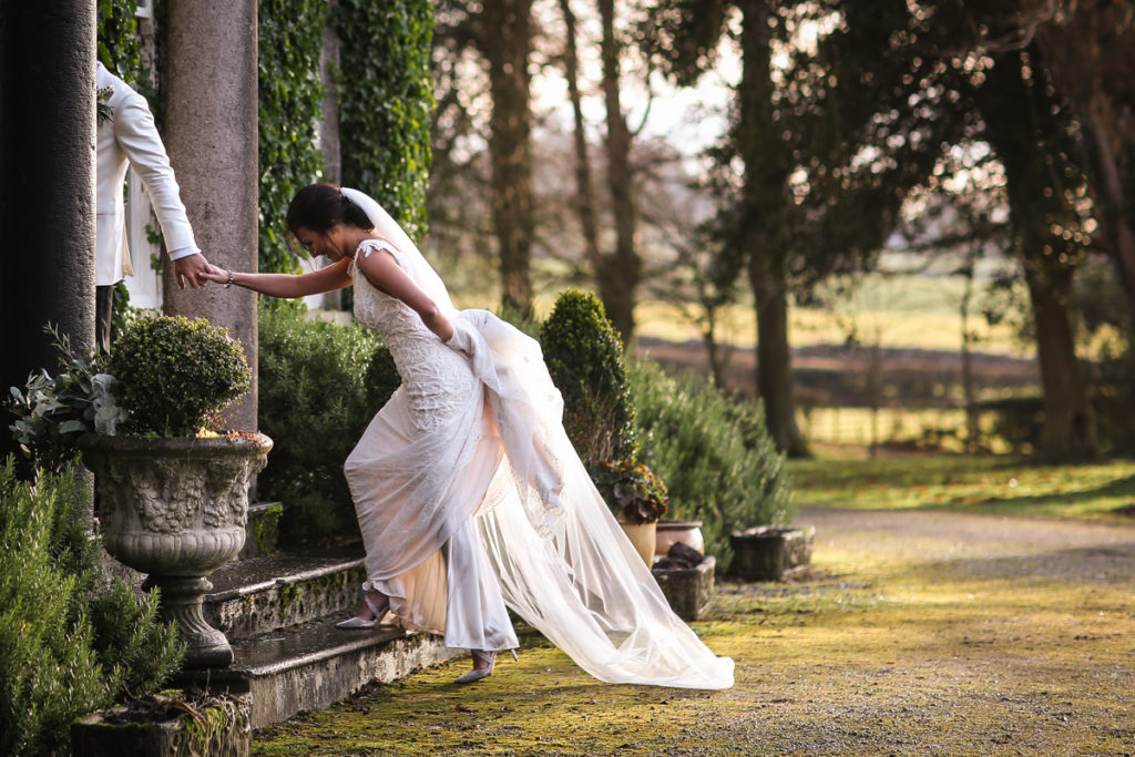 lake district documentary wedding photographer Longlands bride and groom in winter light walking up the steps into the house